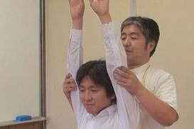 両手を挙げる